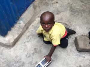 kenyan-breeze-student-playing-with-toy-car-on-floor
